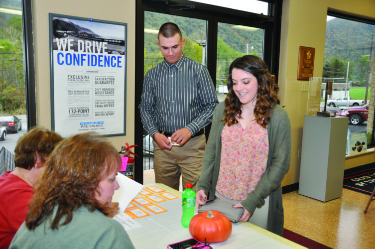 KEVIN RAUCH/FOR THE EXPRESS Lauryn Geisewite and her escort Jacob Jeffries of Loganton will be representing Sugar Valley Rural Charter School this weekend at the 69th annual Flaming Foliage Festival in Renovo. Lauryn is seen here at her first stop for the weekend — registration at K&L Auto Sales in North Bend — where she met other contestants before leaving to join her host family.