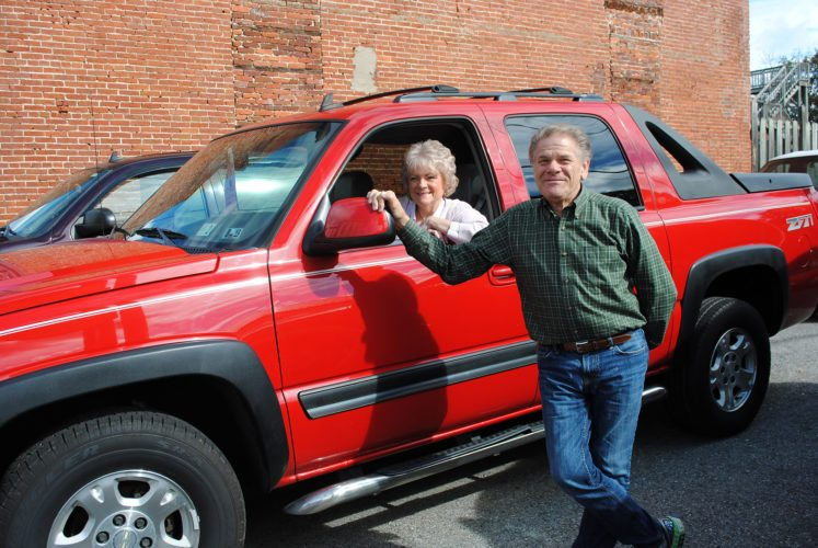 FAITH BRICKLEY/The Express Rusty and Dawn Herlocher pose at their business on North Jay Street in downtown Lock Haven as the couple celebrates 35 years in the auto sales business. The Herlochers say they're blessed to have made so many friends over the years.