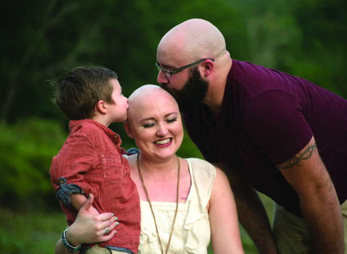 PHOTO PROVIDED In a beautiful show of support following the loss of her hair during cancer treatment, Barbie Barnes is kissed by her son, Sam, and husband, Chad, who also shaved his head in a show of solidarity.