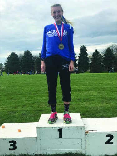 Alyssa Laughner on the podium after becoming Central Mountain's first ever Cross-Country District Champion. (The Express/Scott Baker)