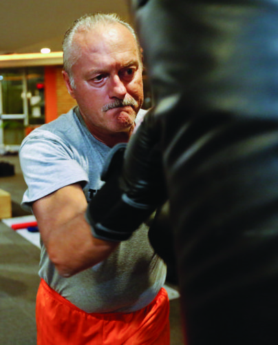 In this Oct. 18, 2017 photo, Jim Brown works the heavy bag during a workout at Unbound Synergy gym in New Hope, Pa. Physical therapists Anne Haneman and Joanne Haug run intense, rigorous boxing training at Unbound Synergy gym for people living with Parkinson's Disease. Clients say it improves mobility and delays the effects of the chronic, progressive movement disorder. (Elizabeth Robertson/The Philadelphia Inquirer via AP)