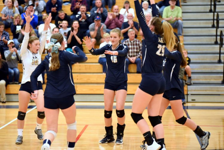 The Eagles huddle around Grace Hugar (16)after recording a score in the team's district 6 semi-final match on Thursday.