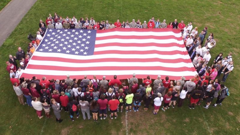 Members of the military and Lock Haven University community hold the flag before last year's Veterans Day game. (Photo courtesy of LHU Football)