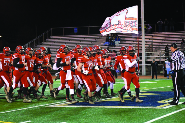 The Bellefonte High School football team runs onto the field before a high school football playoffs game against Greater Johnstown High School. The Red Raiders defeated the Trojans, 34-12, to advance to the next round of the playoffs. (The Express/Tim Weight)