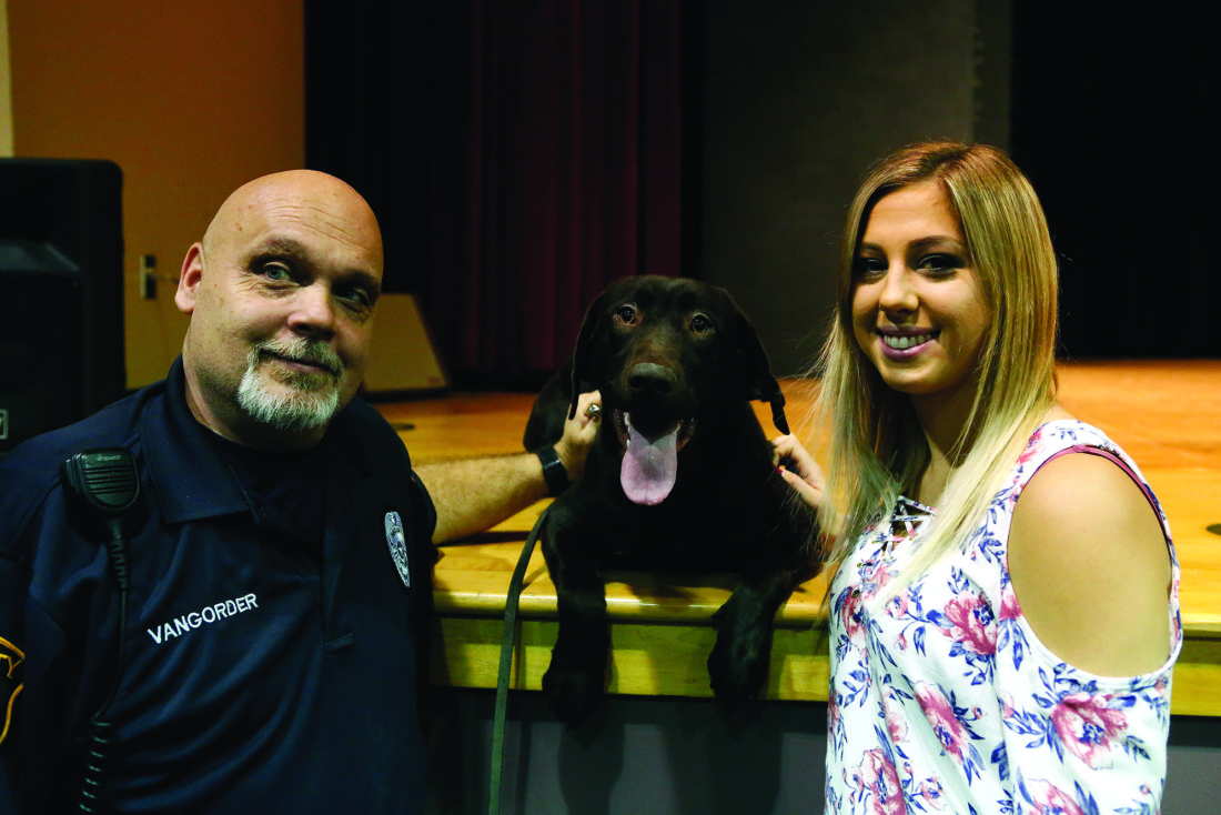 SPENCER McCOY/THE EXPRESS Keystone Central's new drug-sniffing canine Dutchess rests between her handler Scott VanGorder, left, and Erin Gregor, from whom the dog was purchased.