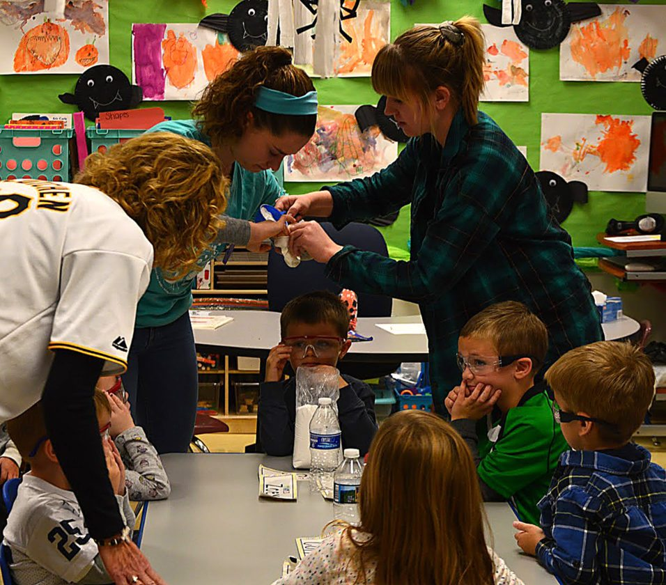 High school seniors Maegan Miller, left, and Macy Akeley did science experiments with preK students, including Expanding Ghosts, Erupting Pumpkins, and Bouncy Balls.