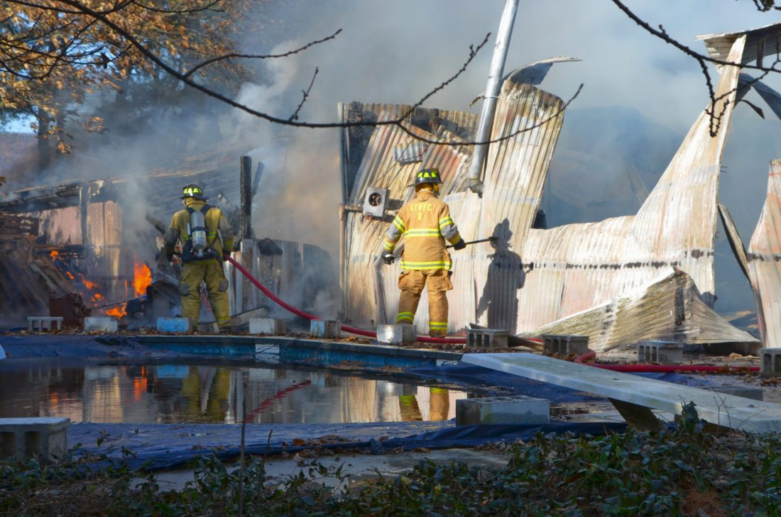 PHIL MAPSTONE/FOR THE EXPRESS Firefighters work on a blaze along Route 64 outside Mill Hall yesterday afternoon. A home was saved from the fire, but a building formerly used as a print shop was lost to the flames.
