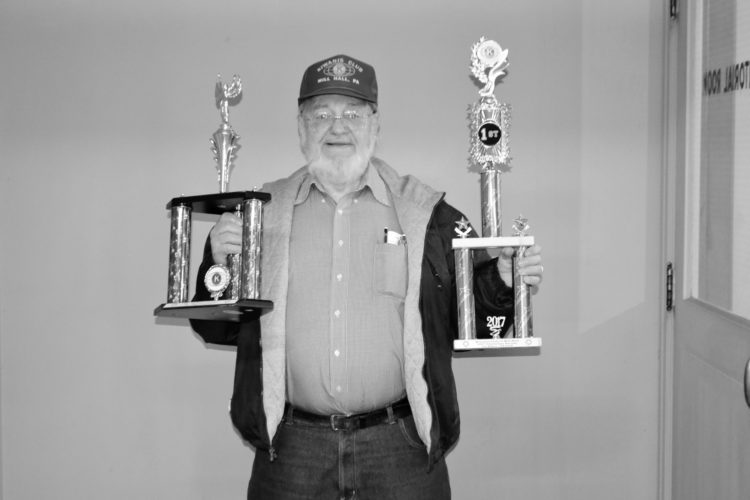 LAURA JAMESON/THE EXPRESS Mill Hall Kiwanis Christmas Parade co-chairman Bob Jackman holds trophies that will be given to top groups at the parade this Saturday in Mill Hall. Cash prizes will also be given to the winners.