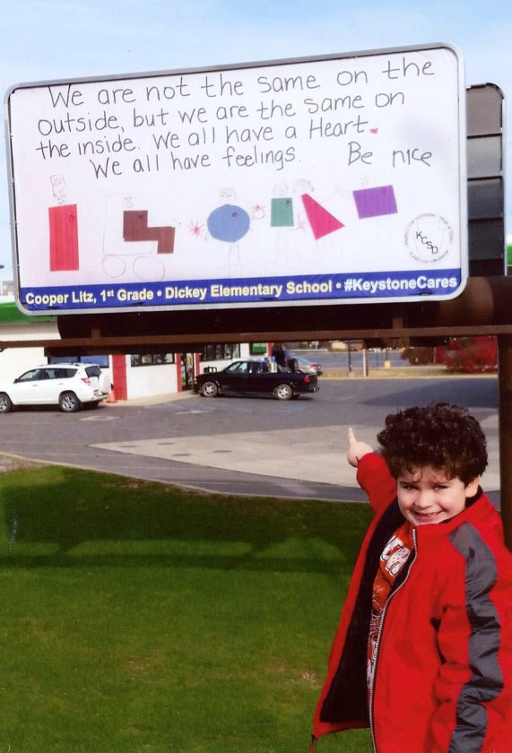 PHOTOS PROVIDED Cooper Litz points to the billboard in Mill Hall that displays his winning poster on diversity.