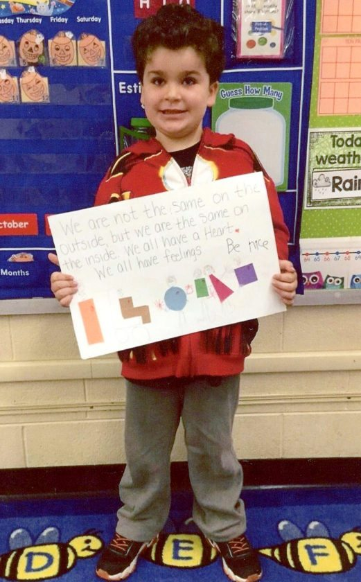 Cooper Litz holds his poster at the front of the class for his fellow first-graders at Dickey Elementary School to see.