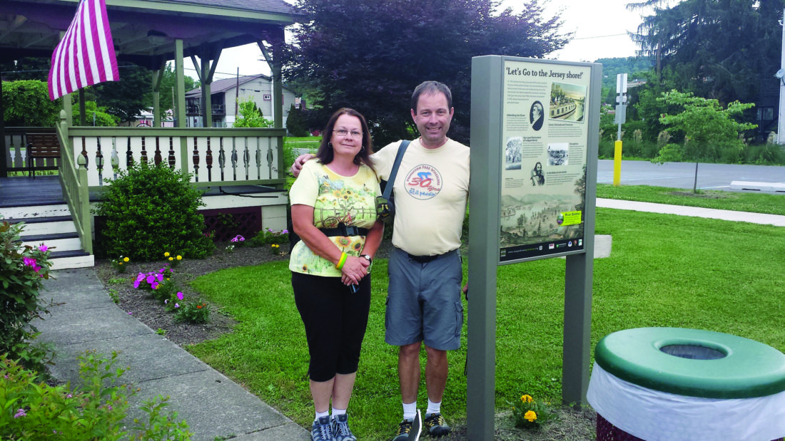 """PHOTO PROVIDED Angela Connolly and Frank Warnock of Ogletown, Del., stand in the public park in Jersey Shore, where they came last summer to ride their bikes on the Pine Creek Rail Trail. Trish Carothers met them and took their photo one evening when she was walking around Jersey Shore before a Borough Council meeting. The couple said they stayed at the Gamble Farm Inn and also explored amid their visit. They said the Inn allowed them to leave their car there several nights while they rode the trail.  But they also said they'd like to have seen more information and maps about the Pine Creek Rail Trail, having had a little difficulty finding the trailhead from the Inn. """"These are things that our community assessments revealed too,"""" said Trish Carothers, program assistant with the Susquehanna Greenway Partnership. """"That is why we are trying to work collaboratively with PA Wilds, DCNR, the visitors bureaus and communities. I think this couple is a good example of the potential these trails have for local economies."""""""