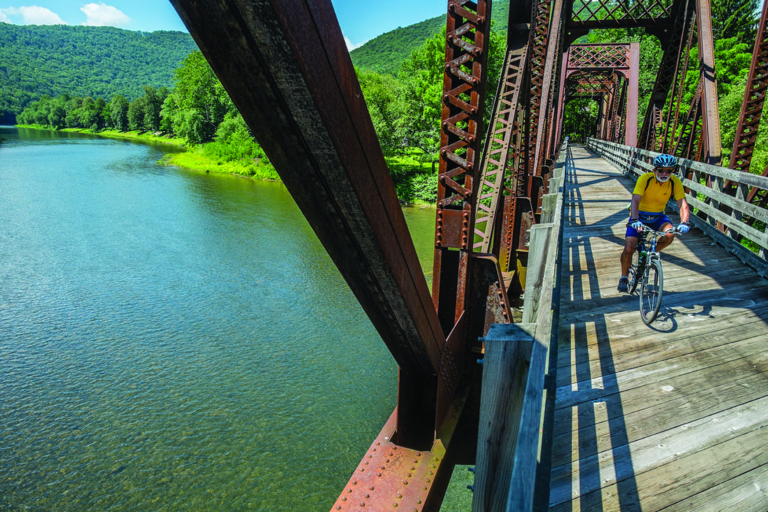 PHOTO PROVIDED  A bicyclist enjoys the Pine Creek Trail which winds along the mountainside and over Pine Creek in Lycoming and Clinton counties.
