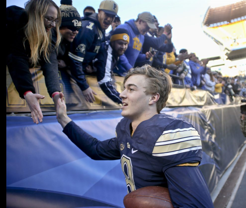Pittsburgh quarterback Kenny Pickett (8) is greeted by fans in the student section after the team defeated Miami in an NCAA college football game, Friday, Nov. 24, 2017, in Pittsburgh. Pittsburgh upset the second ranked, Miami 24-14. (AP Photo/Keith Srakocic)