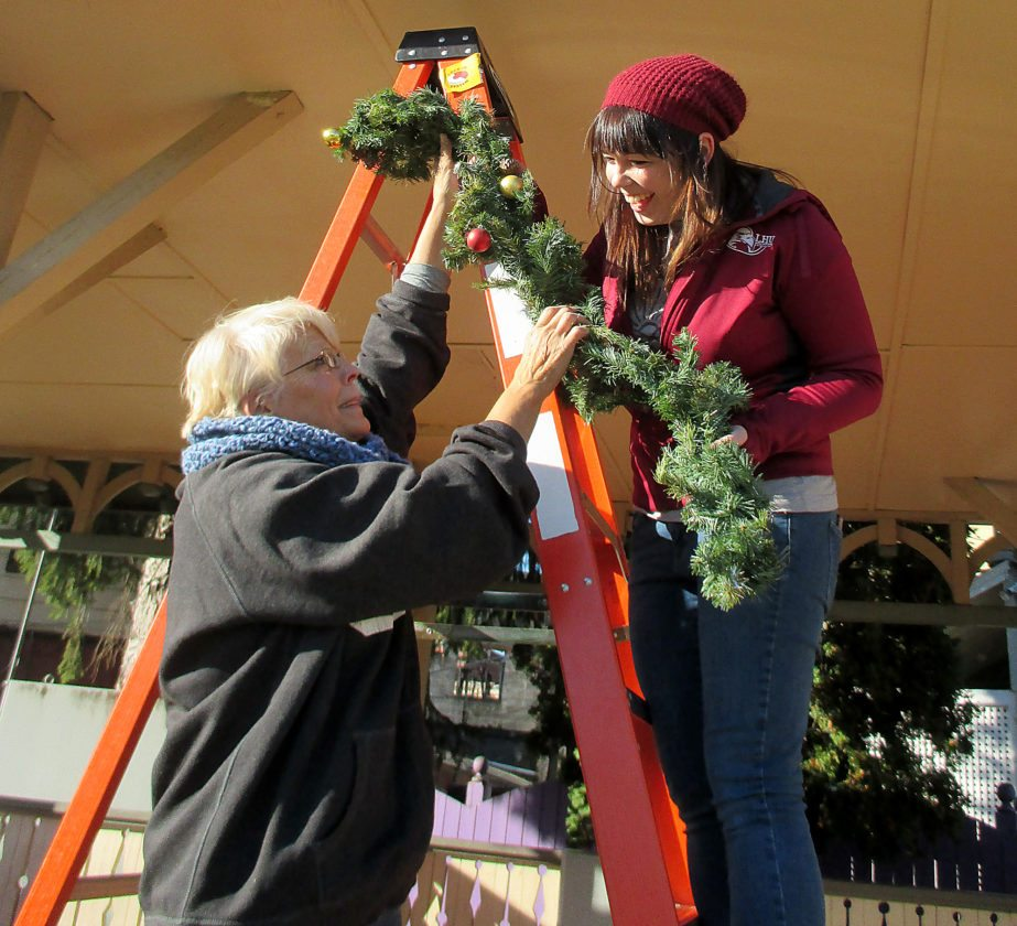 WENDY STIVER/THE EXPRESS Downtown Manager Kasey Blesh, right, and Bonnie Gradel, AmeriCorps worker for Downtown Lock Haven Inc., hang garland on the Triangle Park gazebo, preparing for Haven Holidays this weekend.