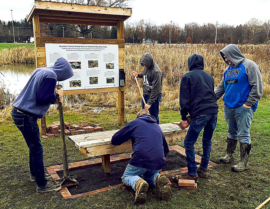 Natural Resource students spend a cold class period laying foundation bricks around benches located at the wetlands at Central Mountain High School.   PHOTOS PROVIDED