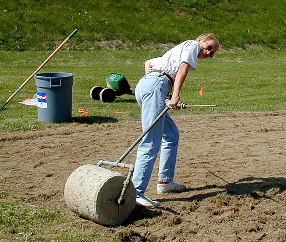 PHOTO BY TOM BUTZLER Tina pulls a concrete roller to prepare seed bed for grass seed in a turf trial.