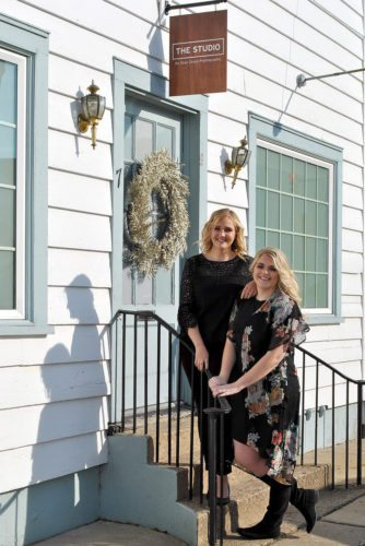 The sister duo (left, Brittany Martin, right, Hannah Rayls) proudly stand in front of their new home at,'The Studio.'