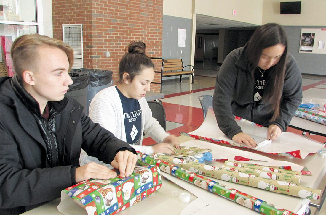 PHOTO by EMMA GOSALVEZ/ THE EXPRESS Students who help organize Bellefonte Area High School's Mini-Thon wrapped presents for community members from 1 to 4 p.m. on Sunday, Dec. 17 as a fundraiser. From left are Eddie Fitzgerald, Keeli Pighetti and Gabbie Pighetti.