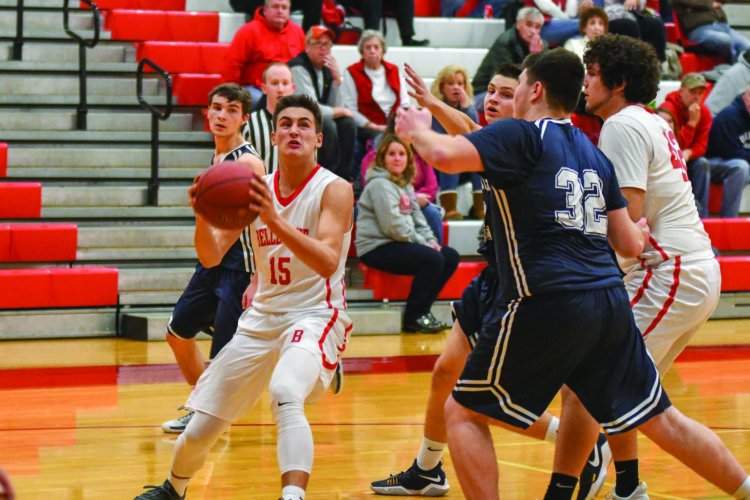 Ben McCartney (15) of Bellefonte High School gets ready to try a layup against the defense of Mifflinburg High School in high school basketball action on Monday night. The Red Raiders lost to the Wildcats, 60-54. (The Express/Tim Weight)