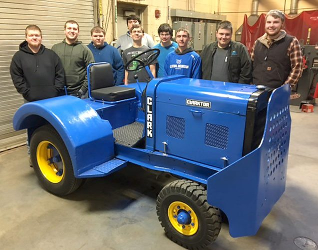 Standing with their rebuilt tractor are, from left, CM students Brandon Wenker, Zane Dutton, Jed Welch, Kage Ginery, Zack Clobe, Richard Grove, Owen Rinker, Colton Dunlap and Connor Tolomay.