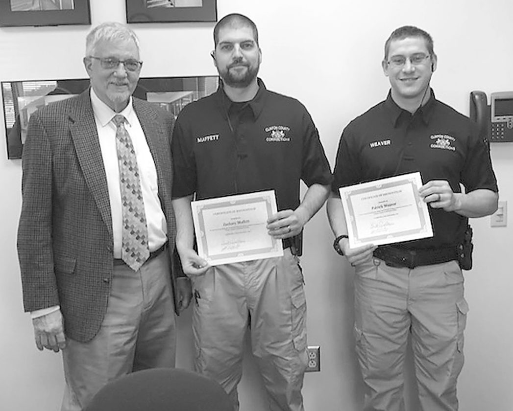PHOTO PROVIDED Correctional officers Zachary Maffett, center, and Patrick Weaver were recognized Wednesday by Warden John Rowley, left, for their outstanding efforts in the performance of their duties at the Clinton County Correctional Facility.