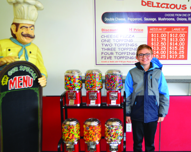 DEREK DANNEKER/FOR THE EXPRESS Grady Bowman stands in front of his candy machines inside Pizza King in downtown Lock Haven.