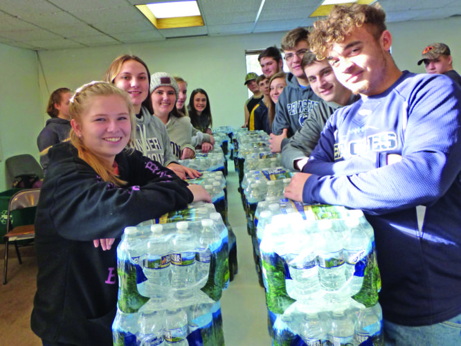 ROSE HOOVER/THE EXPRESS Bald Eagle Area High School students were at the Snow Shoe EMS Building to help with the free bottled water distribution to the residents served by the Mountaintop Regional Water Authority. Through the efforts of Rep. Mike Hanna's office, the water was donated by Nestle Waters.