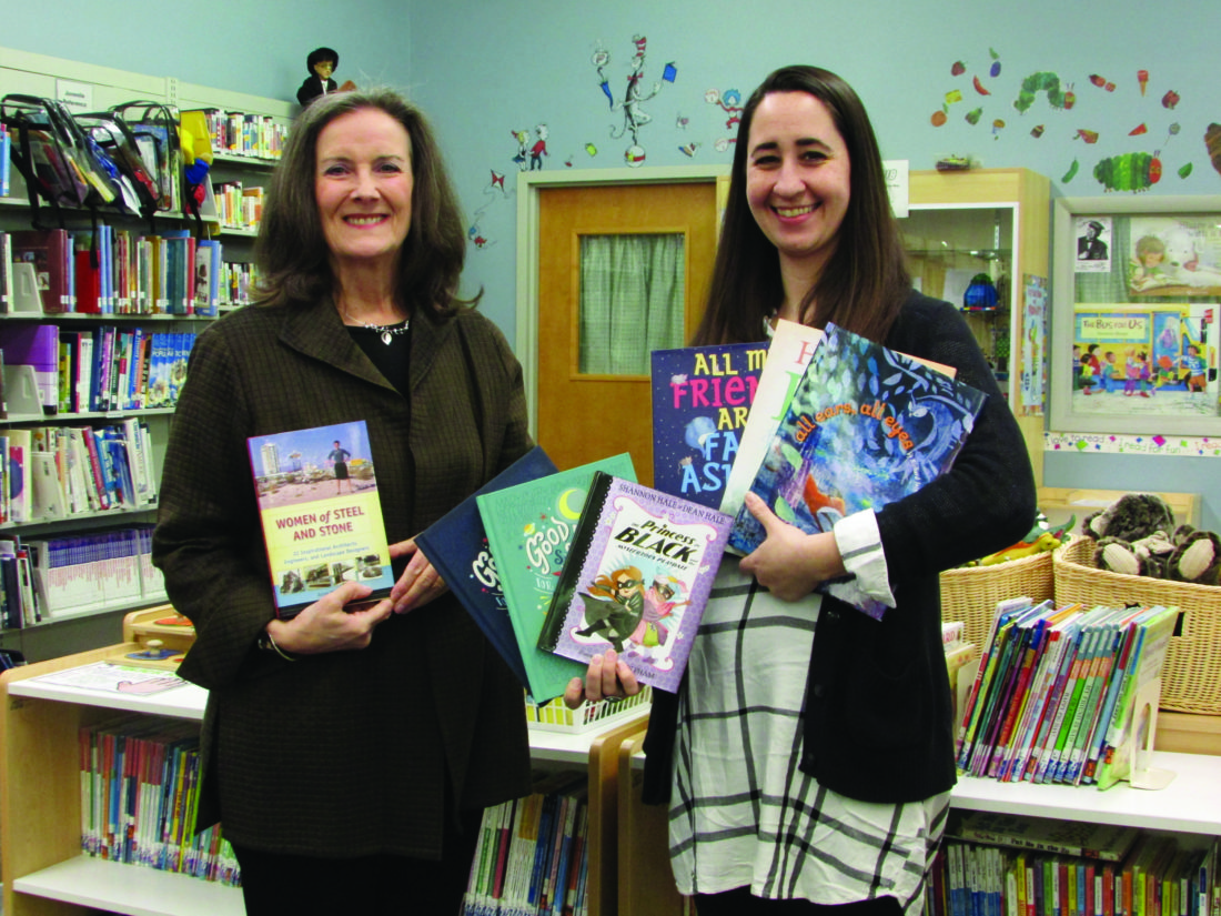 EMMA GOSALVEZ/THE EXPRESS Nancy Perkins, left, great niece of Anna Keichline, and Children's Librarian Laura Sarge display the recently donated books in the children's library at the Centre County Library in Bellefonte.