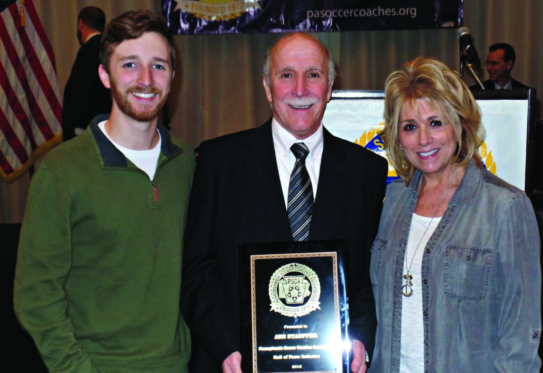 """Abe Stauffer poses for a photo with his wife and son at the ceremony Jan. 27 when he was inducted into the Pennsylvania Soccer Coaches Association Hall of Fame. His son, Zach, played soccer for his dad at Central Mountain. His wife, Coral, can clearly be called a true """"soccer mom"""" since having her husband devote his career to the sport and the two seeing their son play even well before his high school career. The ceremony took place at the PSCA All-State Honor and Awards Banquet in Camp Hill. Approximately 135 high school boys and girls soccer players were recognized for making All-State. Eight coaches were honored for winning state Coach of the Year. A total of 467 people attended the banquet. (Photo Provided)"""