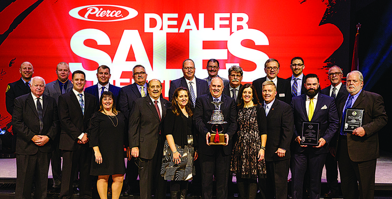 PHOTO PROVIDED Members of Glick Fire Equipment received the Dealer of the Year award from Pierce Manufacturing. Pictured is the sales team, and starting fourth from left are Dave Glick, founder;  current owners Jodi Mohn and Doug Glick (holding trophy), and Amy Sweitzer.