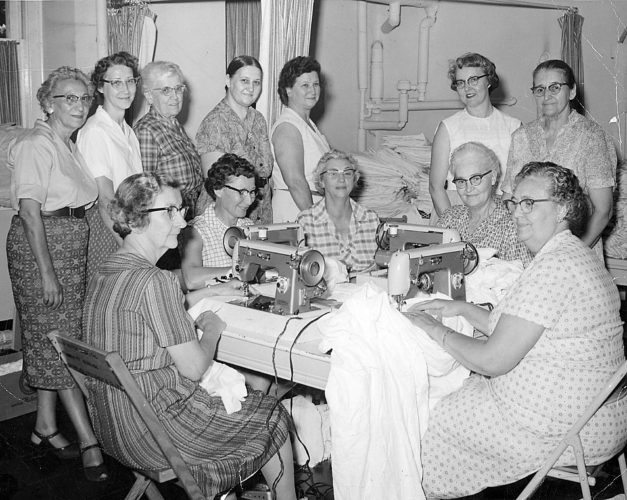 "EXPRESS ARCHIVES 'Original Sewing Group' members recognized Rovena Fenstermacher of Ocala, Fla., a faithful Express reader, called to tell us that Olive Cross Bowman of Mill Hall is the smiling woman seated second from left, and that Mrs. Robert Laird, also of Mill Hall, is seated at far right. In addition, an anonymous reader has told us the woman sitting at the table in a striped dress is Virginia Watkins. We thank them for their help, and would love to learn more names of the women in this photo from our archives. On the back of the photos are the words ""Original Sewing Group;"" the information that Zimmerman, a Lock Haven photographer, took the photo; and only seven names: Mrs. Edith Shampansky, Mrs. Ada Sorgen, Mrs. Mable Dumm, Mrs. Naomi Myers, Mrs. Martha Gerarity, Mrs. Lois Conway and Mrs. Ruth Peters. Might they be the women standing in the back? If you can help, please contact Wendy Stiver at The Express at 570-748-6791 or wstiver@lockhaven.com."