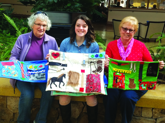 "PHOTO PROVIDED Lauryn E. Geisewite, center, a senior at Sugar Valley Rural Charter School, got together with mentor Brenda Mitchell, right, and her grandmother Sue Walizer, left, to make 40 ""fidget pads"" for local residents in long-term care facilities. The ""fidget pads"" are typically used for residents with altered cognition. There are many activities on the pads for the residents to do, to help maintain simple life skills and dexterity. They vary from tasks such as buttons, zippers, clasps and hooks, to more sensory activities such as a horse's mane to brush, soft fleece dolls, tulle and packing bubbles. Lauryn held fundraisers to purchase the items needed, and she also received some cash donations. She is sharing her labor of love with nursing home residents at Susque-View Home, Manor Care, The Haven and Fulmer's. Lauryn never sewed before starting this project and has learned a life skill as a result. She plans to study nursing in college and hopes to work in a trauma unit."