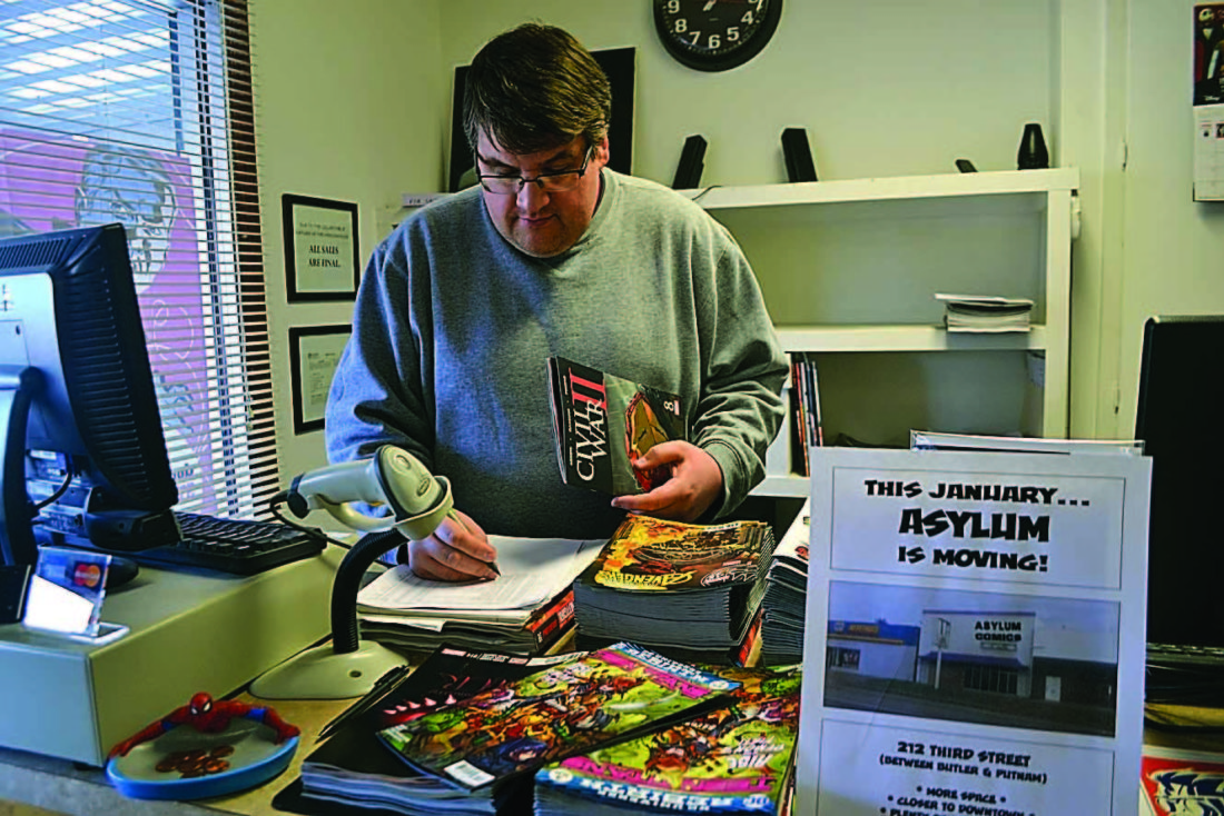 SAM SHAWVER   The Marietta Times Jordan Lowe, owner of Asylum Comics, sorts through some new arrivals at the store's current location on Muskingum Drive Tuesday. The business is moving and will reopen at 212 Third St. next Tuesday.