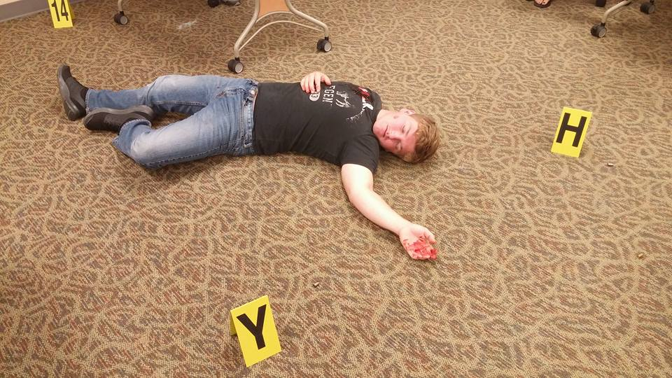 Among the many demonstrations of YES Days, WSCC's Criminal Justice Club staged a crime scene. Students were encouraged to review the situation, collect evidence and develop plausible motives and culprits. Shown is WSCC Criminal Justice Club Treasurer Daniel Newlen posing as a gunshot victim at a crime scene.