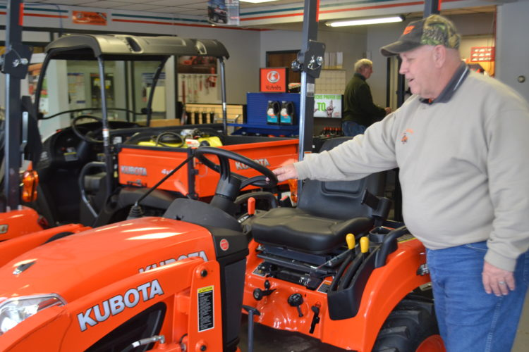 PEYTON NEELY   The Marietta Times Roger Moorison, store manager for Lashley Tractor Sales, inspects one of the lawn mowers at the Marietta store on Friday afternoon.
