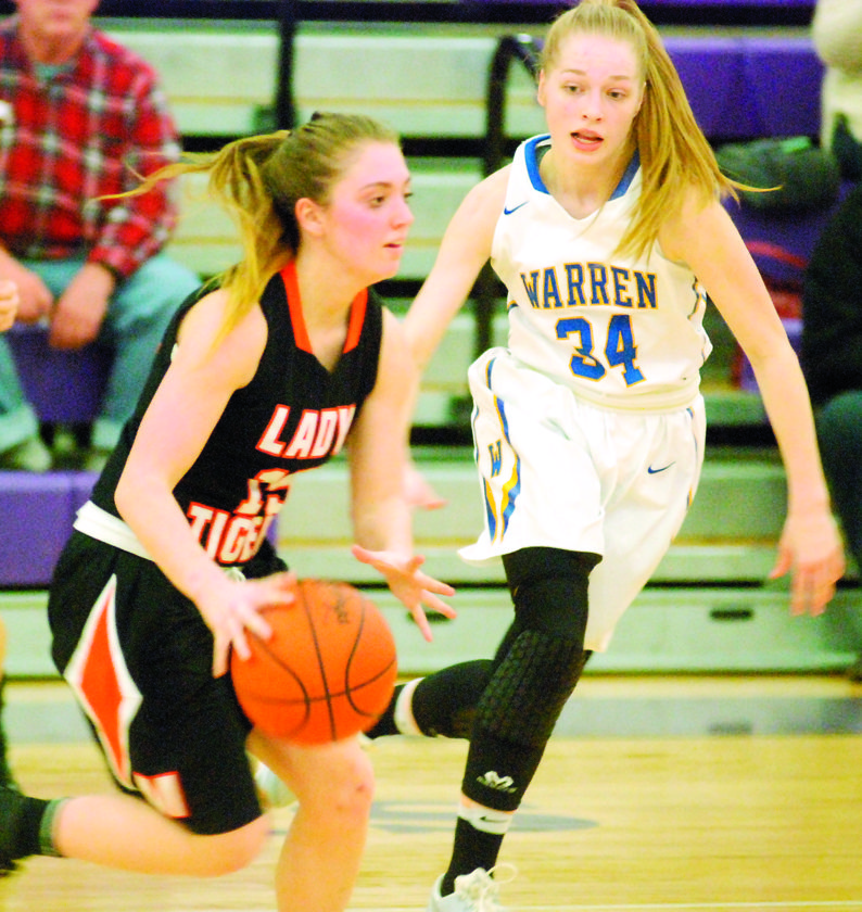 MIKE MORRISON The Marietta Times Marietta's Torrance Nonnenmacher, left, dribbles the ball as Warren's Molly McCutcheon defends during a high school girls sectional basketball game Thursday in Logan. Warren won, 47-38.