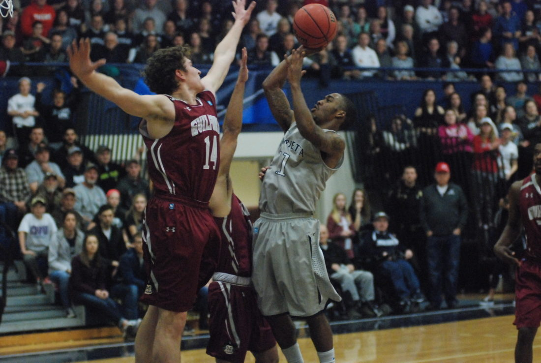 JORDAN HOLLAND The Marietta Times Marietta College's Keith Richardson (11) goes up for a basket as Guilford's Carson Long (14) defends during an NCAA Division III men's basketball tournament game Saturday at Ban Johnson Arena. Richardson finished with 19 points as the Pioneers won, 88-64.
