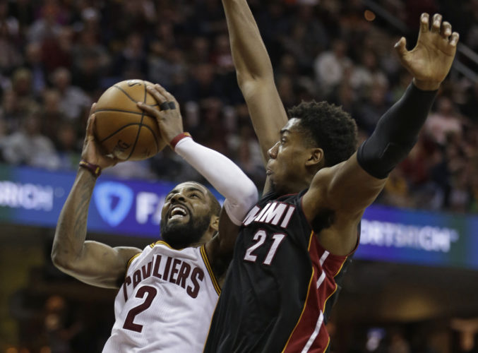 Cleveland Cavaliers' Kyrie Irving (2) shoots against Miami Heat's Hassan Whiteside (21) in the first half of an NBA basketball game, Monday, March 6, 2017, in Cleveland. (AP Photo/Tony Dejak)