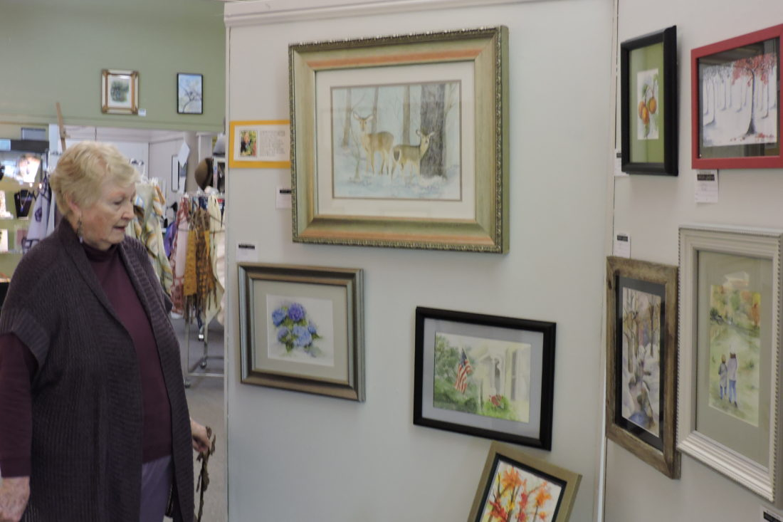 SAM SHAWVER   The Marietta Times Riverside Artists Gallery member Jane Ryals looks over watercolor paintings by students of local artist Lynda Rhodes in the gallery at 219 Second St. Tuesday.