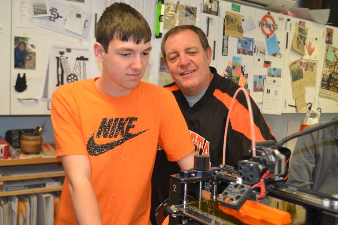 PEYTON NEELY   The Marietta Times Senior Scott Schofield, 17, and industrial arts teacher Steve Foutty work with a 3-D printer during class at Marietta High School on Thursday.