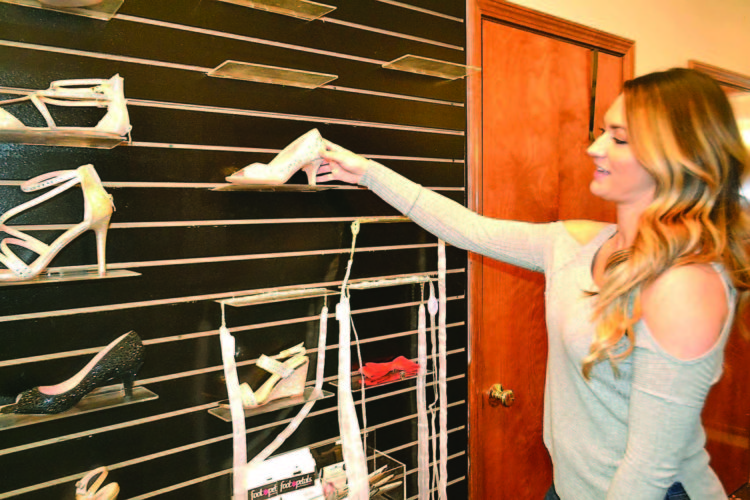 PEYTON NEELY   The Marietta Times Kristina Davis, owner of Elizabeth Michaels in Vienna, stocks shoes at her store on Monday afternoon.