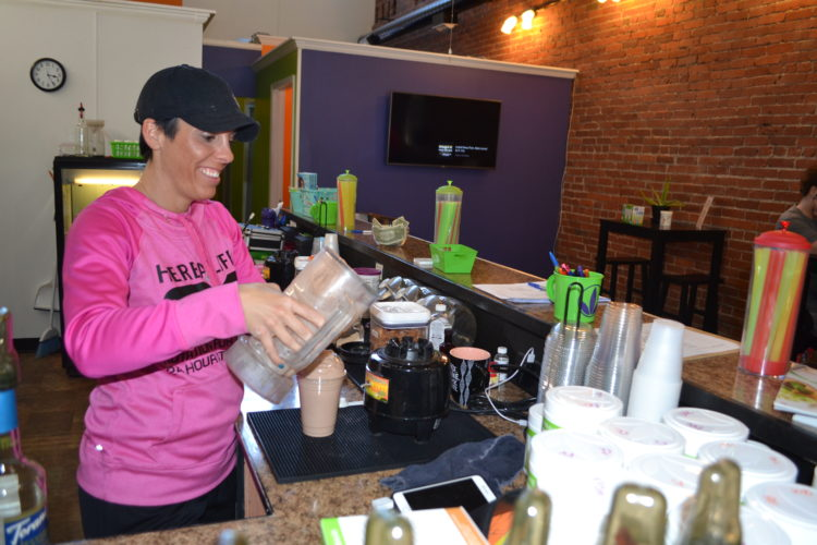 ERIN O'NEILL   The Marietta Times Shayne Byers, owner of Healthy Start Nutrition on Front Street, mixes a meal replacement shake for a client Wednesday. Byers' business was one of the establishments in Marietta that had no violations at its last health inspection.