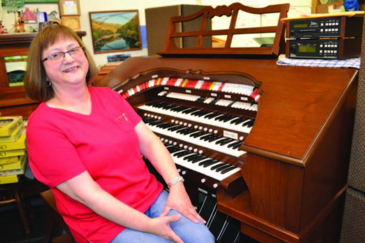 ERIN O'NEILL  The Marietta Times Diana Shuck, an employee of American Flags and Poles and an organist at Twin Rivers Baptist Church, demonstrates the Allen electric organ that she will be playing during May's First Fridays event. The 20-year-old instrument is currently housed at the store on Front Street.