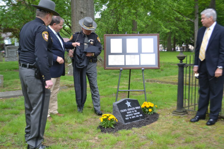 PEYTON NEELY   The Marietta Times Washington County Sheriff Larry Mincks, left, along with Wood County Sheriff Mark Wasylyshyn, center, and other members of the Buckeye State Sheriffs' Association unveil the new marker at the grave site of Col. Ebenezer Sproat at Mound Cemetery on Friday morning.
