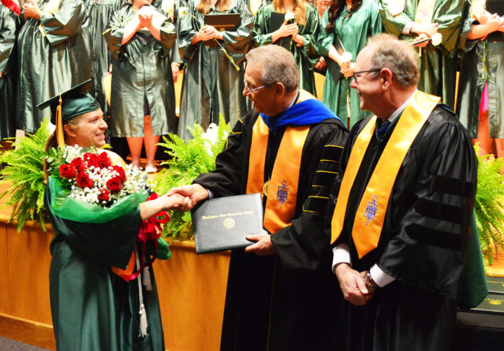 DOUG LOYER  Special to the Times Suzanne Paugh, WSCC's 10,000th graduate in 45 years is presented a bouquet of flowers by President Bradley Ebersole and Mark Nutter, Vice President for Academic Affairs.