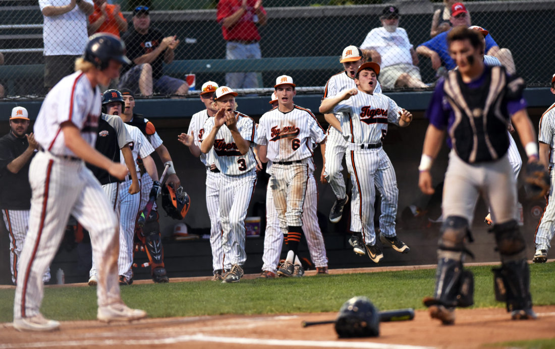 Marietta players celebrate after Zach Deskins scored a run during Wednesday's district final game against Unioto in Athens.  Photo courtesy of Sam Blackburn/Times Recorder