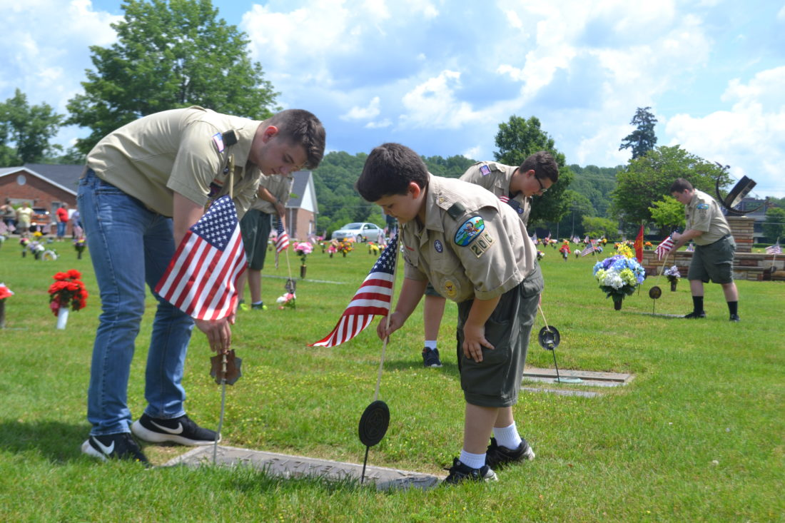 PEYTON NEELY   The Marietta Times Members of Boy Scout Troop 200 Braison Tubaugh, 16, left, and Austin Harrow, 12, adjust the flags they placed on the grave sites of veterans at the East Lawn Cemetery in Reno on Memorial Day Monday.