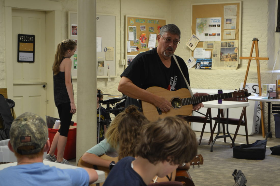 ERIN O'NEILL  The Marietta Times Instructor Mark Doebrich talks to students during the 16th annual High Schools That Rock guitar camp at the First Unitarian Universalist Society on Monday.