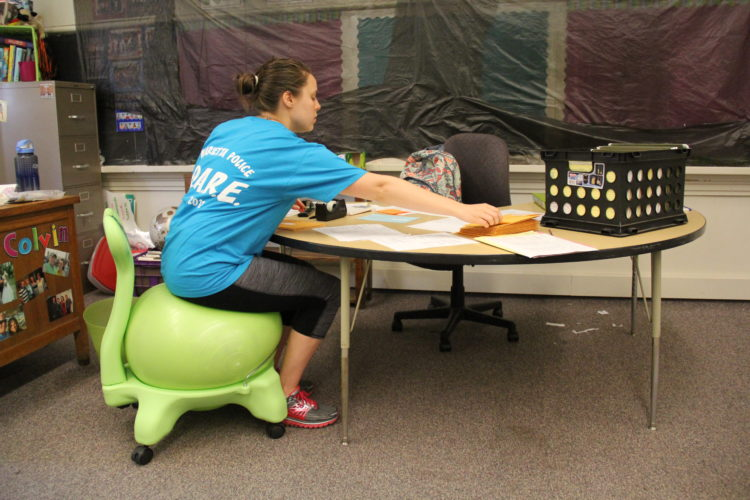 JANELLE PATTERSON   The Marietta Times Bethany Colvin, a fifth-grade teacher at Washington Elementary, finalizes grades for her students while sitting on a stability ball Monday.