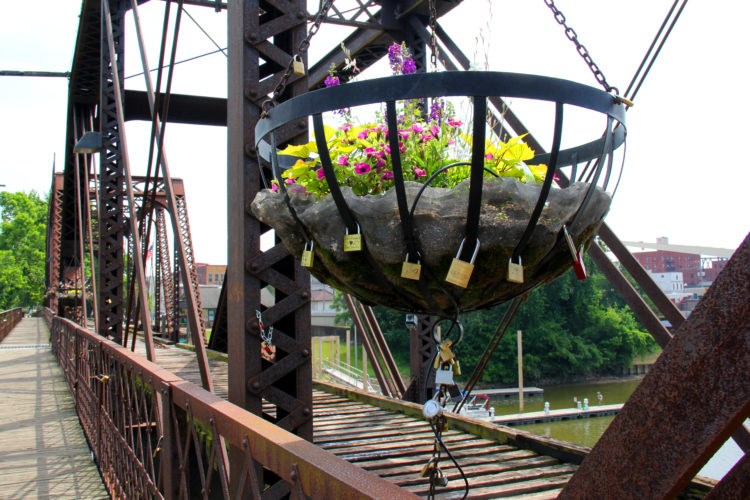 JANELLE PATTERSON   The Marietta Times Locks secured to hanging baskets Monday on the Historic Harmar Railroad Bridge will be removed at the close of summer.